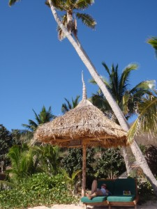 the thatched umbrella and lounge chairs in front of our bure